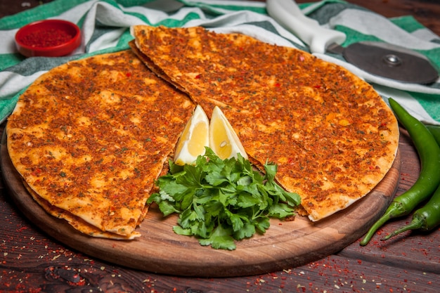 Side view lahmacun with lemon and parsley and green pepper in board cookware