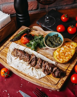 Side view of lamb kebab with baked potato and vegetables on a wooden board