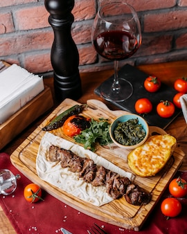 Side view of lamb kebab with herbs and vegetables on a wooden board