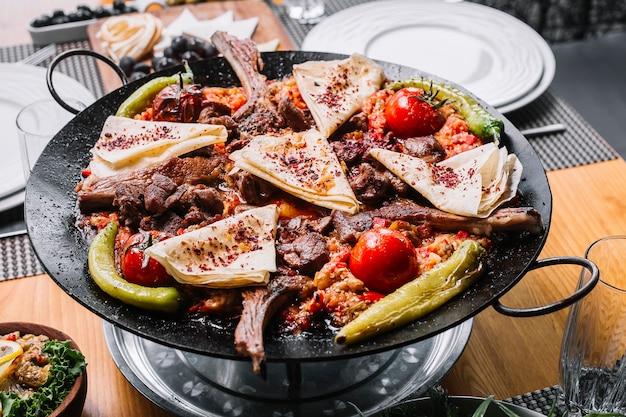 Вид сбоку ребрышки ягненка на гриле с луком, болгарским перцем, помидорами, острым зеленым перцем и лавашем с сушеной барбарисом