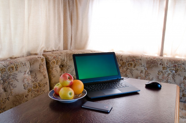 Side view of a laptop in a cozy kitchen with a plate of fruit, a smartphone. break