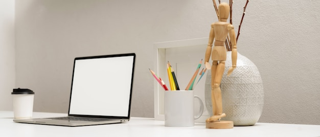 Side view of laptop with clipping path on white table with stationery and decorations in home office