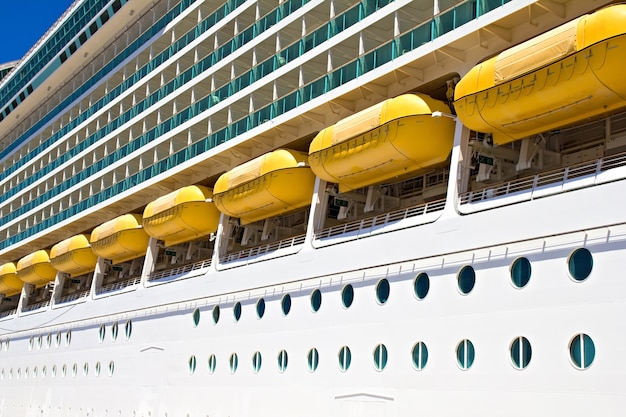 A side view of a large cruise ship showing the main deck with lifeboats