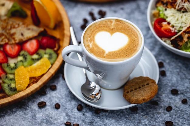 Вид сбоку кофе латте с шоколадным печеньем и кофейными зернами на столе