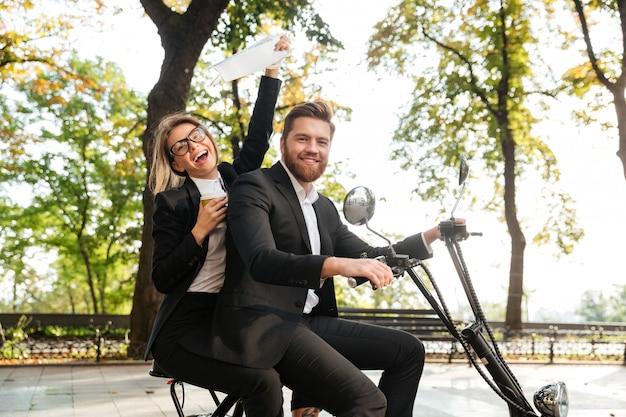 Side view of laughing elegant couple rides on modern motorbike