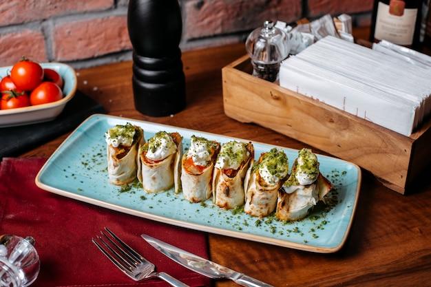 Vista laterale dei rotoli di lavash con salsa acida e pistacchi di verdure su un tavolo di legno