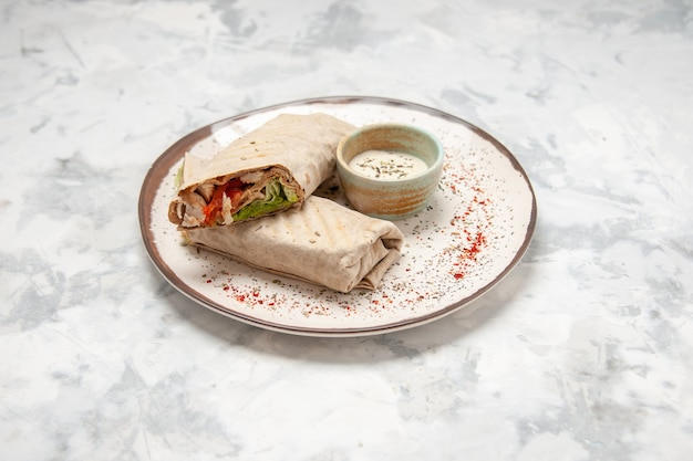 Side view of lavash wrap and yogurt in a small bowl on a plate on stained white surface