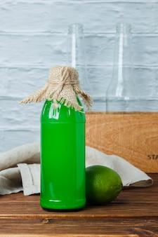 Bottiglia di succo di limone vista laterale con cassa di legno e panno bianco su superficie in legno e bianca. spazio verticale per il testo