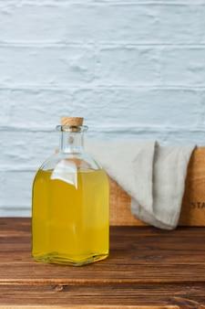 Barattolo di succo di limone vista laterale con cassa di legno e panno bianco su superficie in legno e bianca. spazio verticale per il testo