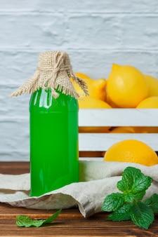 Вид сбоку лимонный сок с лимонами на деревянном ящике, листья на деревянной и белой поверхности. вертикальное пространство для текста