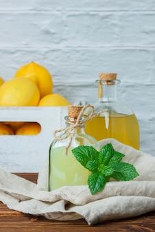木製と白い表面の木製の木枠にレモンとレモンジュースの側面図。テキスト用の垂直スペース