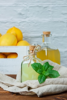 Side view lemon juice with lemons on wooden crate on wooden and white surface. vertical space for text