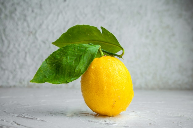 織り目加工の白い背景の上の葉でサイドビューレモン。横型