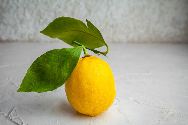 Side view lemon with leaves on white textured background. horizontal