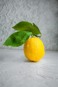 Side view lemon with leaves on white textured background. vertical space for text