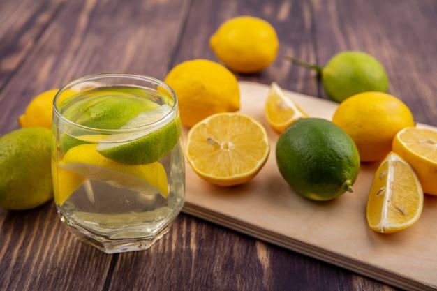 Limoni vista laterale con limette su un tagliere con un bicchiere di acqua detox su uno sfondo di legno