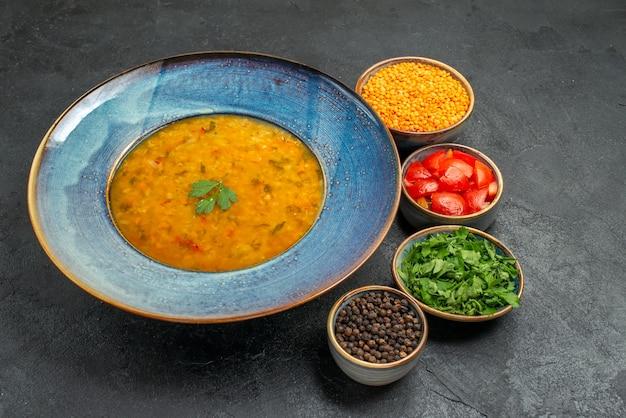 Вид сбоку суп из чечевицы суп из чечевицы рядом с мисками томатов приправы, травы