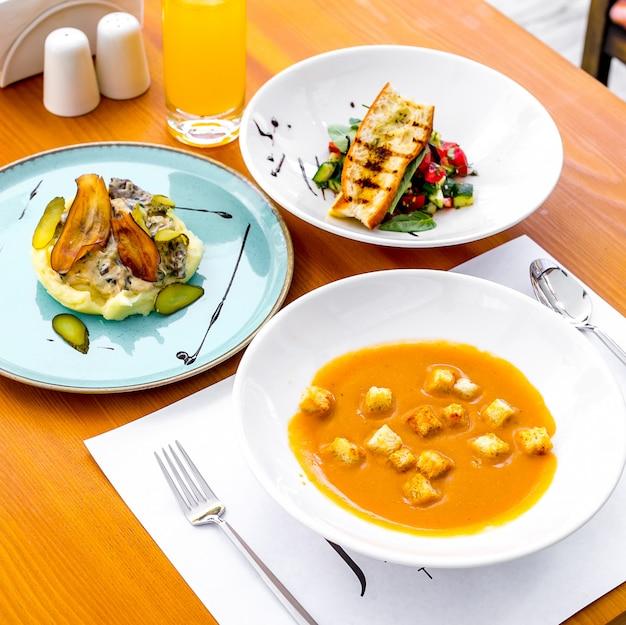 側面図レンズ豆のスープ、クラッカー、マッシュポテト野菜サラダ、ジューステーブルの上