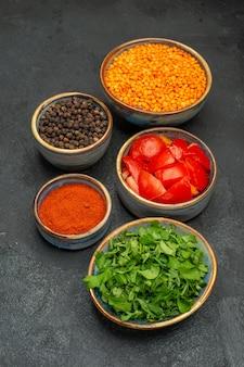 Вид сбоку чечевица, специи, чечевица, травы, помидоры на темном столе