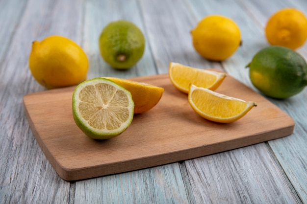 Side view lime wedges with half orange and lemon on a cutting board