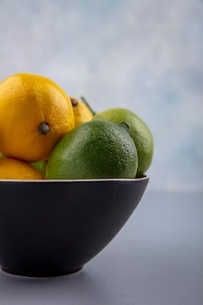 Side view limes and lemons in a black bowl on a gray background