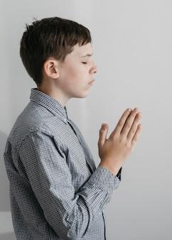 Вид сбоку маленький мальчик молится