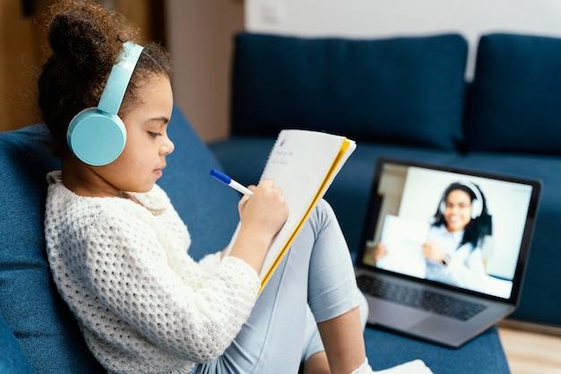 Vista laterale della bambina durante la scuola in linea con laptop e cuffie