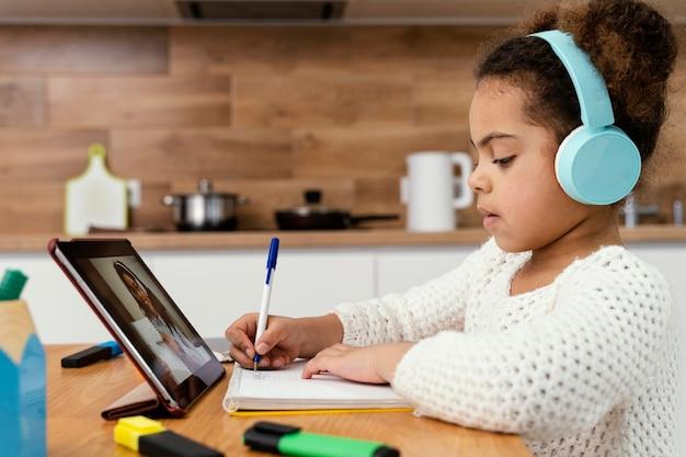Vista laterale della bambina durante la scuola online con tablet