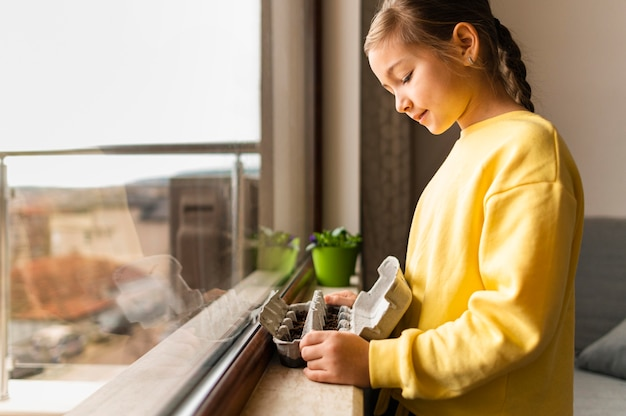 Side view of little girl holding planted seeds in egg carton