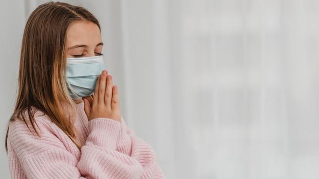 Vista laterale della bambina che prega con mascherina medica e copia spazio