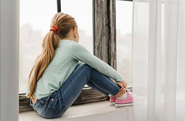 Bambina di vista laterale che si siede sul davanzale di una finestra