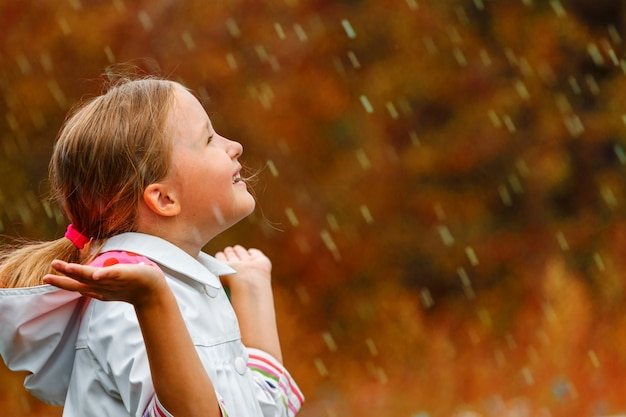 Side view of a little girl standing in autumn park in the rain.