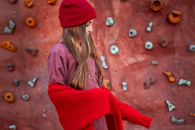 Side view little girl standing next to a climbing wall