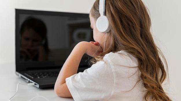 Vista laterale della bambina utilizzando laptop con le cuffie