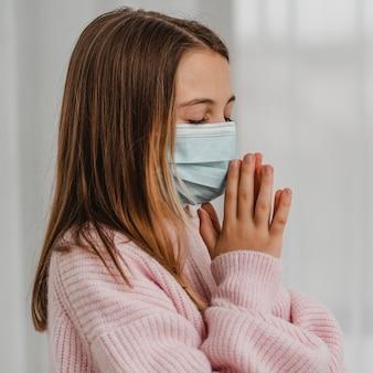 Vista laterale della bambina con la mascherina medica che prega