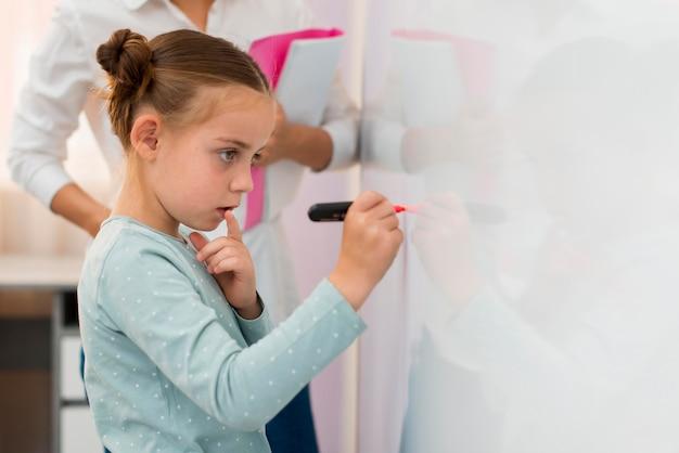 Маленькая девочка пишет на белой доске рядом со своим учителем, вид сбоку