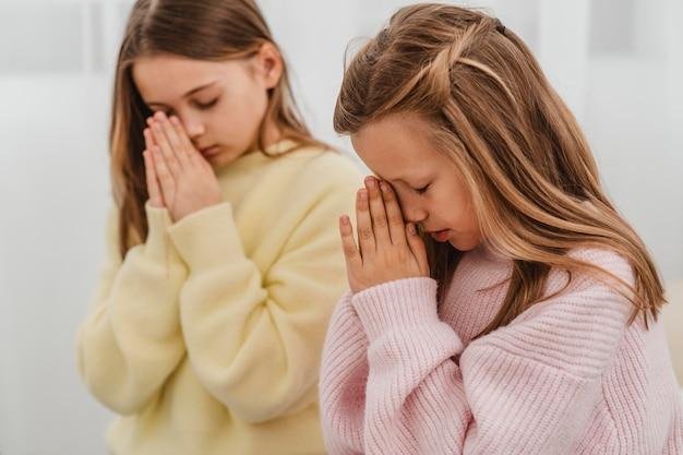 Vista laterale di bambine che pregano a casa