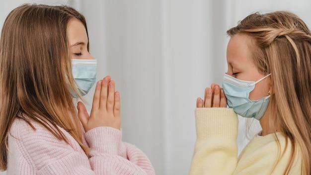 Vista laterale di bambine che pregano con maschere mediche