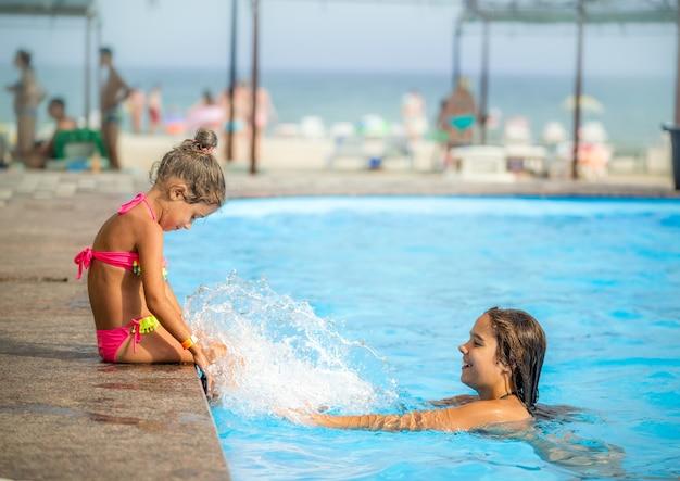 측면 보기 어린 소녀 자매들은 화창한 여름날 열대 지방에서 휴가를 보내는 동안 수영장에서 수영을 하고 서로에게 물을 뿌립니다. 어린이 휴식 개념