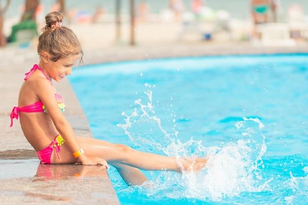 側面図小さな女の子の姉妹はプールで泳ぎ、休暇中にお互いに水をはねかけます