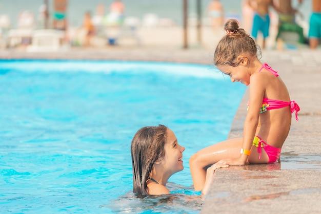 측면보기 어린 소녀 자매는 수영장에서 수영