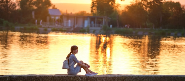 Side view of lonely woman sitting alone on lake shore on warm evening. solitude and relaxing in nature concept.