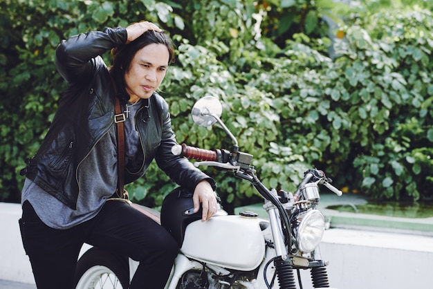 Side view of long-haired biker in leather jacket posing at his motorbike outdoors