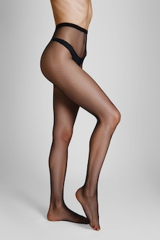 Side view of long sexy female legs in fishnet tights with one leg bent in knee and on tiptoe