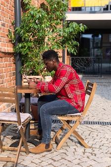 Colpo lungo di vista laterale dell'uomo seduto al tavolo
