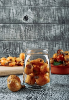 Side view loquats in jar on gray textured background. vertical, space for text