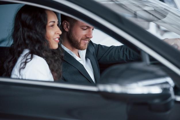 측면보기. 자동차 살롱에서 새 차를 시도하는 사랑스러운 성공적인 부부