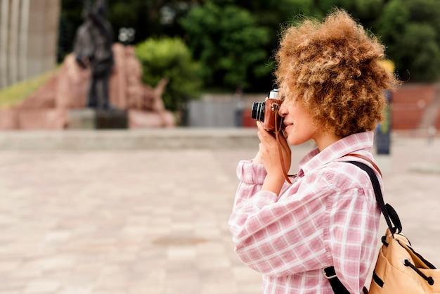 Вид сбоку прекрасная женщина, делающая фото с копией пространства