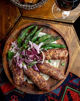 Side view of lula kebab with red onions  sumakh and grilled green chili peppers on a wooden board on the tablejpg
