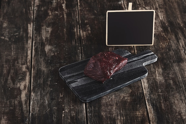 Side view of luxury raw piece of whale meat steak on black marble stone cutting desk and aged vintage wooden table and chalk board price tag